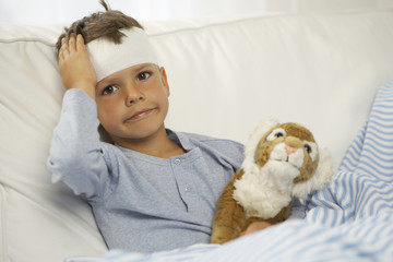 Portrait of a boy showing the bandage on his forehead