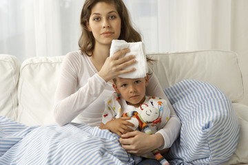 Portrait of a mid adult woman giving treatment to her son suffering from fever