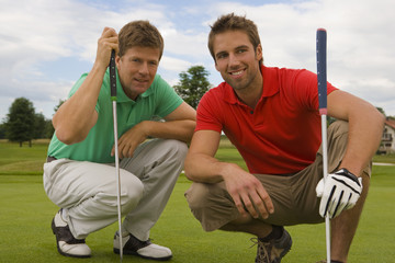 Two mid adult men crouching on a golf course and smiling