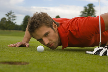 Side profile of a mid adult man judging a golf ball in a golf course