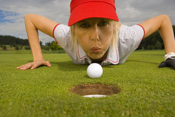Portrait of a mid adult woman blowing a golf ball towards a hole