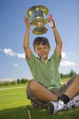 Portrait of a boy holding a trophy over his head and smiling