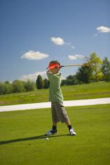 Side profile of a boy swinging a golf club