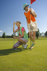 Two mid adult women playing golf