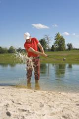 Mid adult man swinging a golf club in waterhole on a golf course
