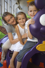 Portrait of a mid adult woman with two children sitting in a caterpillar train