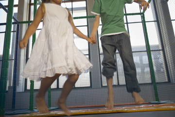 Low section view of a girl with a boy jumping on a trampoline
