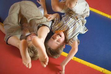 High angle view of two boys playing on an inflatable bouncy castle