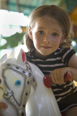 Portrait of a girl sitting on a rocking horse