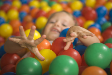 Close-up of a girl lying in a ball pool