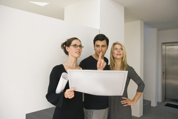 Two businesswomen and a businessman discussing blueprint in an office
