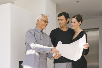Two businessmen and a businesswoman discussing a blueprint in an office