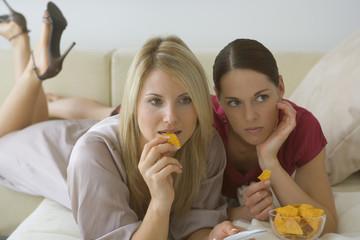 Two women eating crisps
