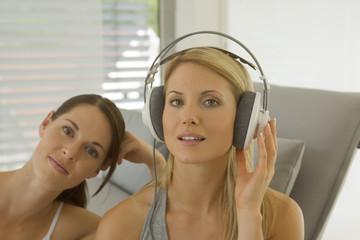 Portrait of two women, one wearing headphones