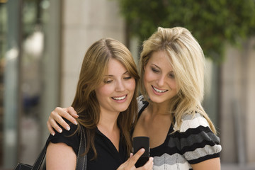 Happy young women looking at cell phone together