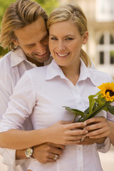 Portrait of a young man embracing a young woman holding a flower and smiling