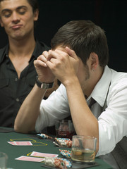 Worried man looking at playing cards at poker game
