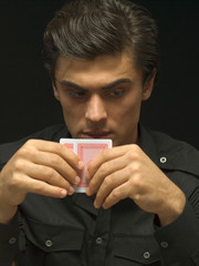 Man thinking and holding playing cards