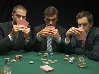 Men holding playing cards at poker game