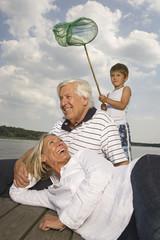 Happy grandparents and grandson near lake