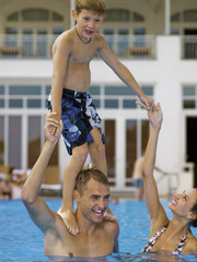 Son standing on father's shoulders in pool