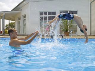 Boy doing back flip in pool