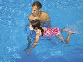 Man teaching girl how to swim