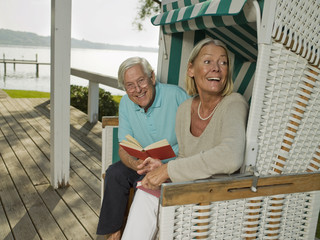 Senior couple reading near lake