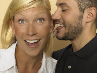 Man whispering in woman's ear