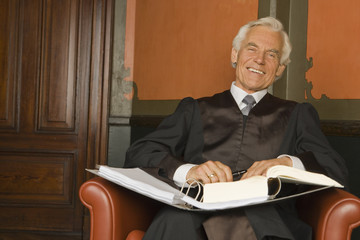 Portrait of a lawyer sitting in an armchair and smiling