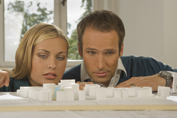 Two architects looking at an architectural model
