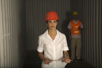 Portrait of a female dock worker holding a clipboard and a man standing behind her in a cargo container
