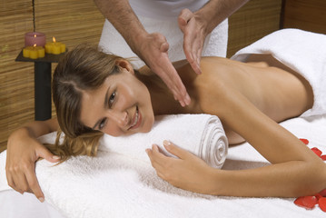 Portrait of a young woman receiving a massage from a massage therapist
