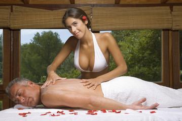 Side profile of a mature man receiving a back massage from a young woman massage therapist