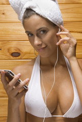 Portrait of a young woman having sauna and listening to an MP3 player