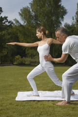 Yoga instructor teaching yoga to a young woman