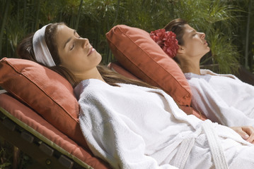 Two young women resting on lounge chairs