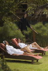 Two young women in bathrobes and resting on lounge chairs