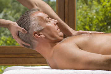 Side profile of a mature man receiving a massage from a massage therapist