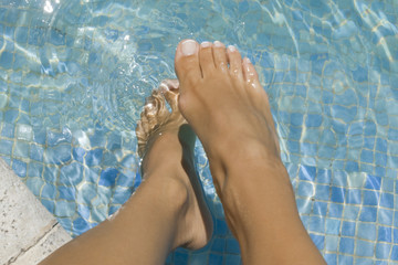 Low section view of a woman's feet in a swimming pool