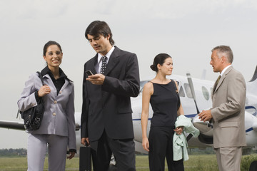 Two businesswomen and businessmen at an airport