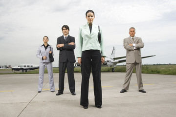Two businessmen and two businesswomen standing at an airport