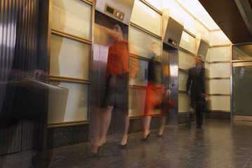 Motion shot of businesspeople walking past elevators