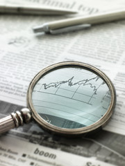 View of graph in newspaper through magnifying glass