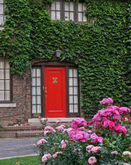 red front door with vines and roses
