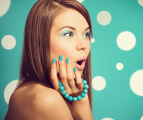 Young beautiful surprised woman holding a turquoise bracelet wit