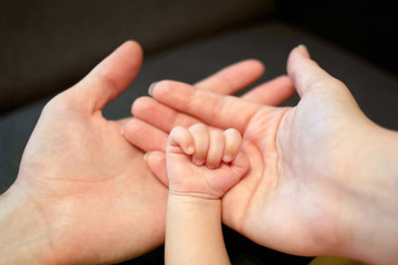 Hands of father, mother and newborn baby.