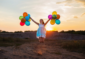 Happy girl with colorful balloons at sunset