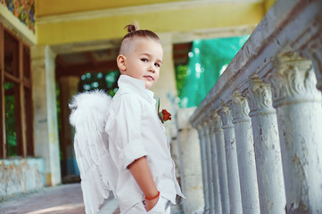 boy with angel wings on old city background