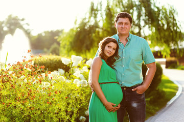 Happy and young pregnant couple. Toned image